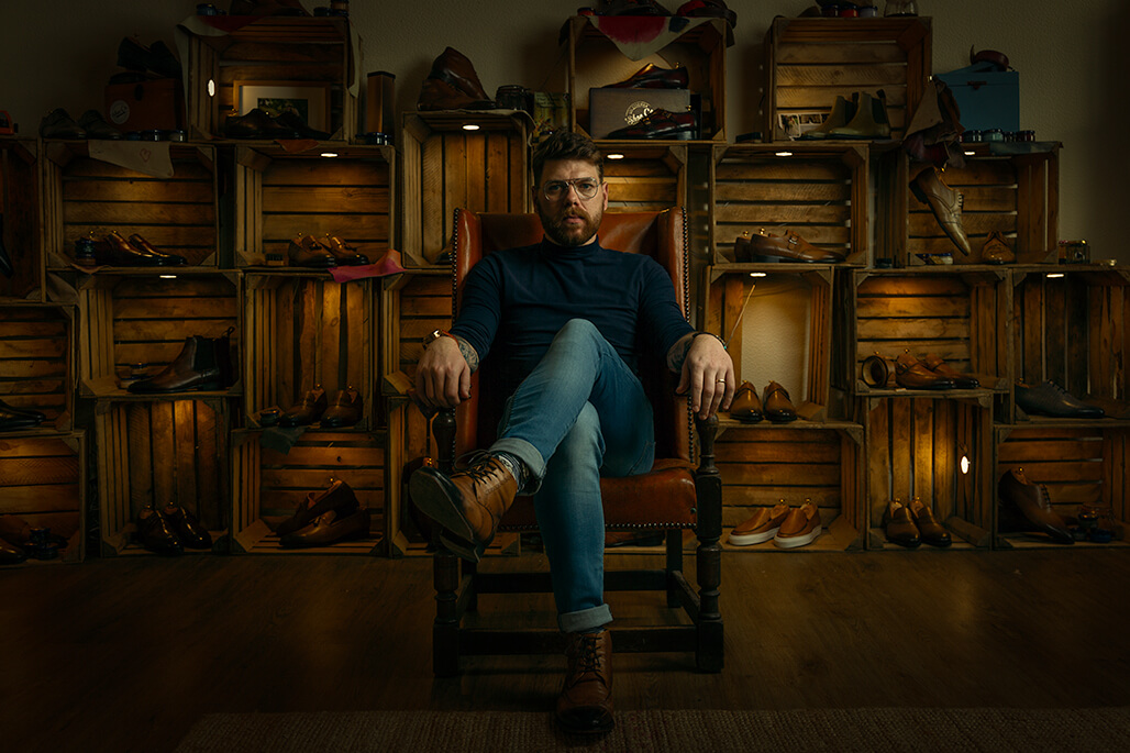 man sitting in-front of shoes