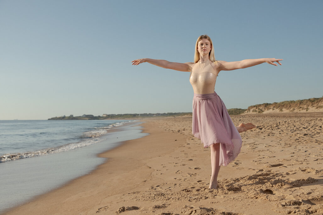 girl dancing in ballet dress on the beach