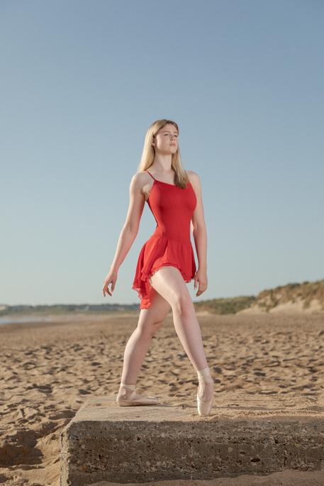 girl in red ballet dress on beach